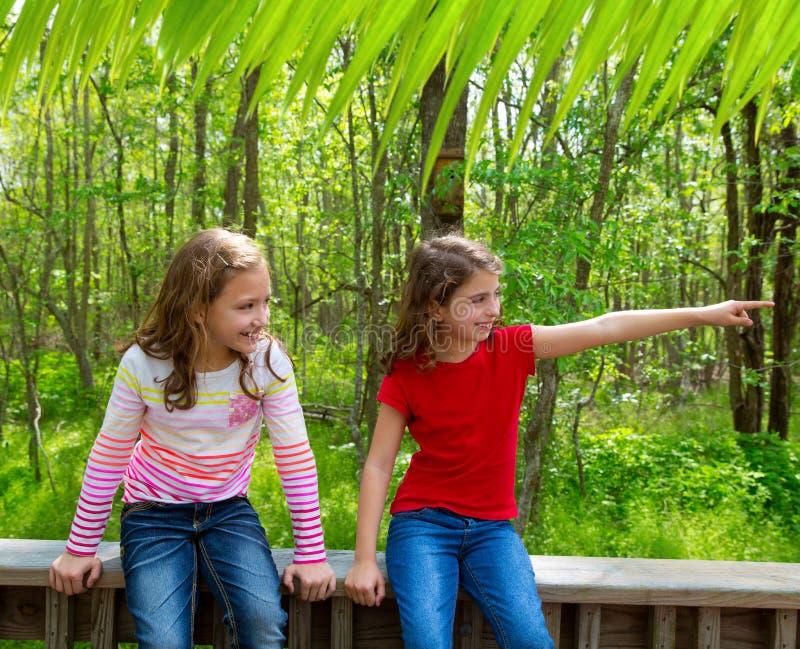 Amigos das crianças que jogam apontando o dedo ao parque da selva fotografia de stock royalty free