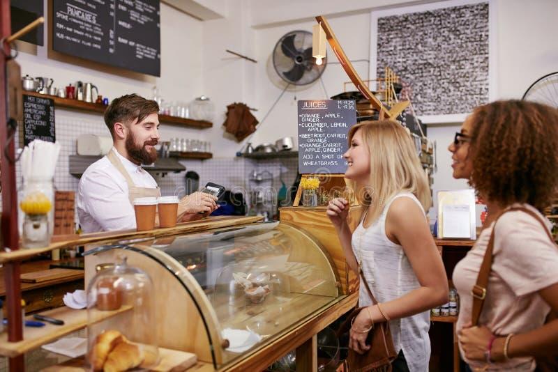 Amigos das jovens mulheres que colocam uma ordem em uma cafetaria foto de stock royalty free