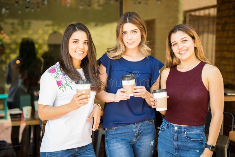 Amigos das mulheres com café fora do café imagem de stock royalty free