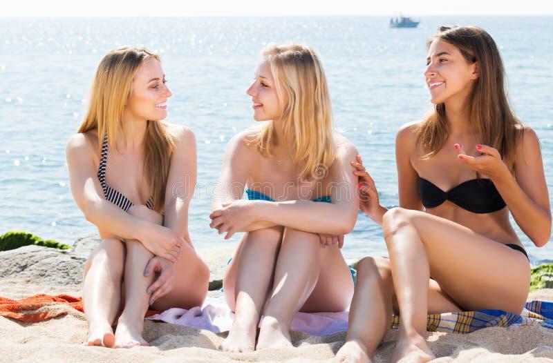 Amigos das mulheres no discurso do biquini fotos de stock