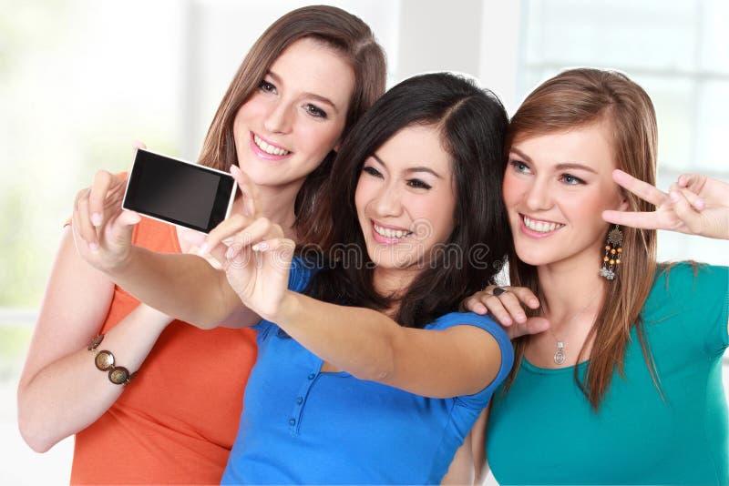 Amigos de chica joven que toman una imagen de ellos mismos imagenes de archivo