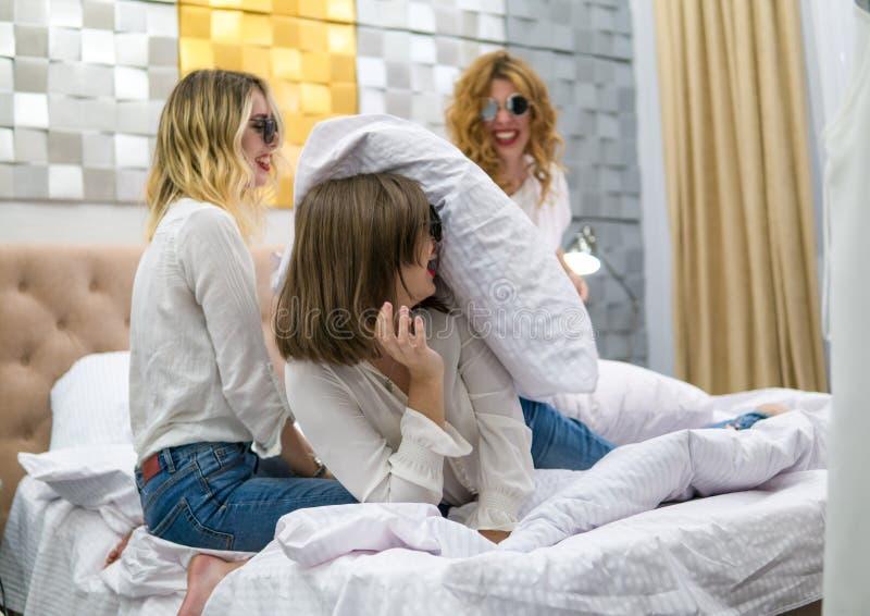 Amigos de chicas jóvenes que luchan las almohadas en el dormitorio fotografía de archivo libre de regalías