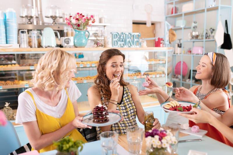 Amigos de inquietação que dão a sobremesas doces seu colega de antecipação imagens de stock