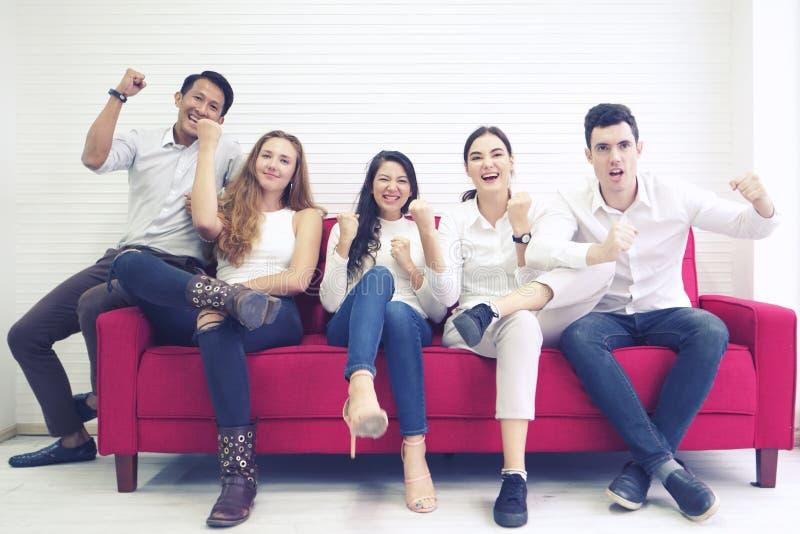 Amigos de la comunidad del grupo de personas de la diversidad que tienen la diversión y risa felices junto, sentándose en el so fotografía de archivo