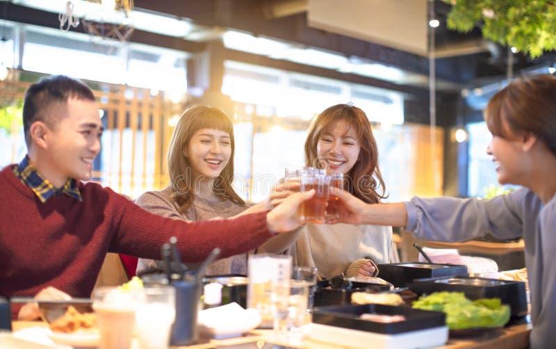 Amigos de la gente joven que tuestan y que comen en el restaurante imagenes de archivo