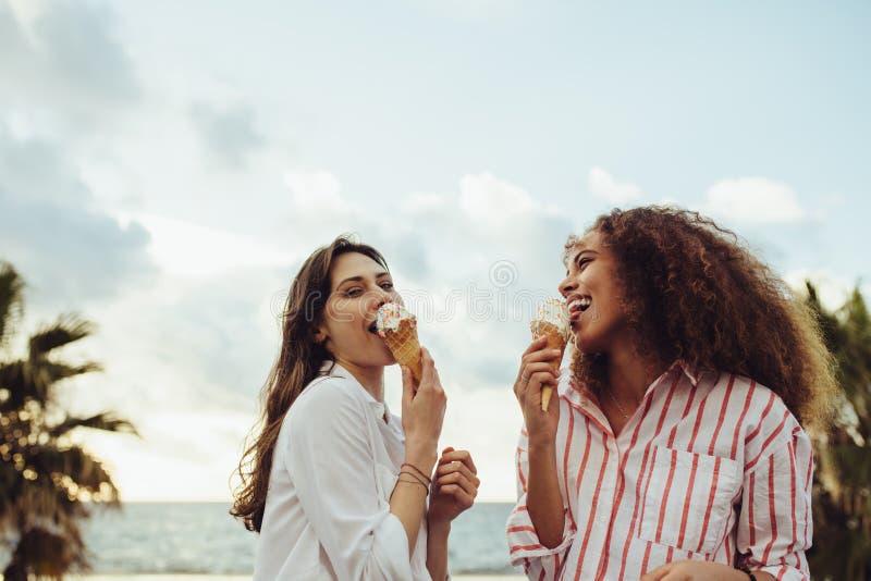 Amigos de la mujer que comen el helado junto foto de archivo libre de regalías