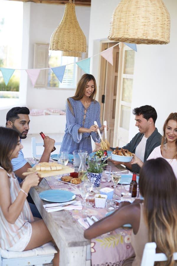 Amigos de la porción de la presentadora en un partido de cena en un patio, Ibiza imagen de archivo libre de regalías