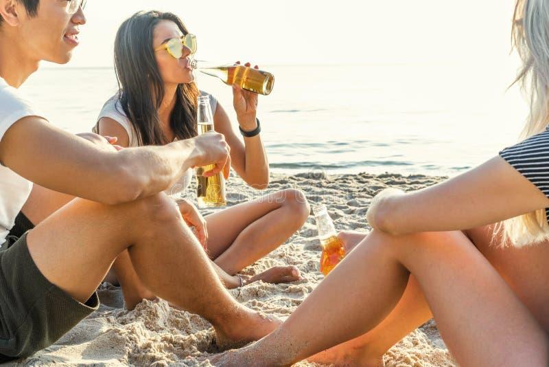 Amigos de la raza mixta que se divierten en la playa Grupo de gente joven feliz que se sienta junto en la playa que habla y fotografía de archivo libre de regalías