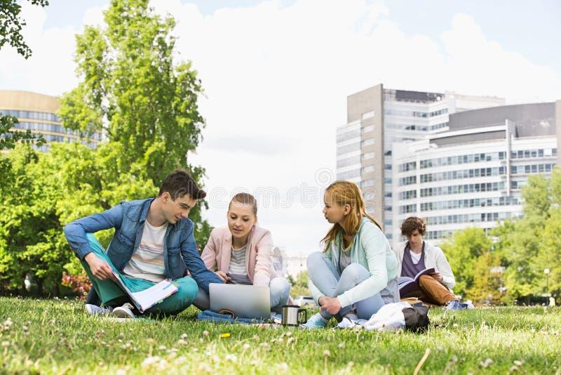 Amigos de la universidad que estudian mientras que usa el ordenador portátil en el campus fotografía de archivo