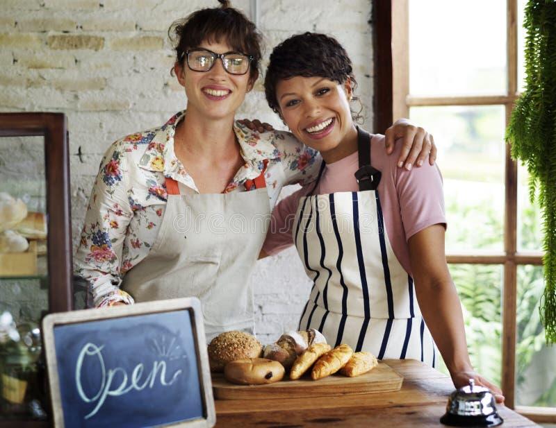 Amigos de las mujeres de la sociedad de la pequeña empresa en la sonrisa de la tienda de la panadería fotos de archivo
