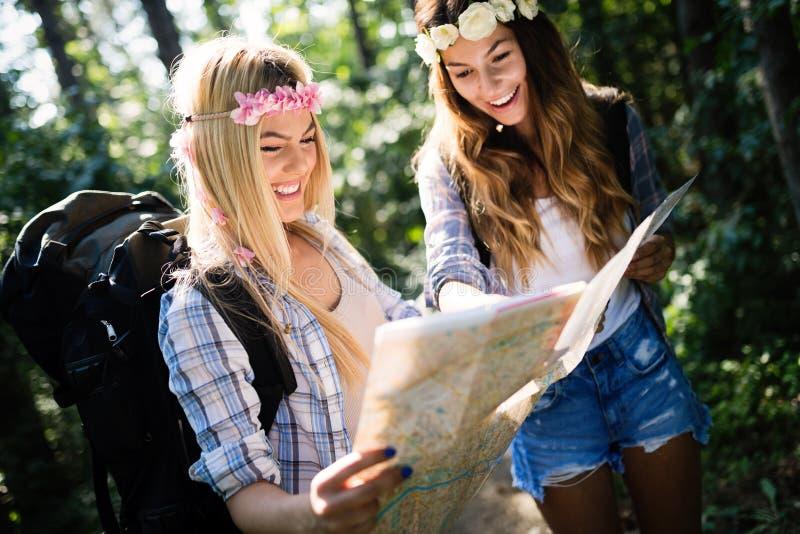 Amigos de las mujeres del caminante con la mochila que caminan en la trayectoria en bosque del verano fotografía de archivo libre de regalías