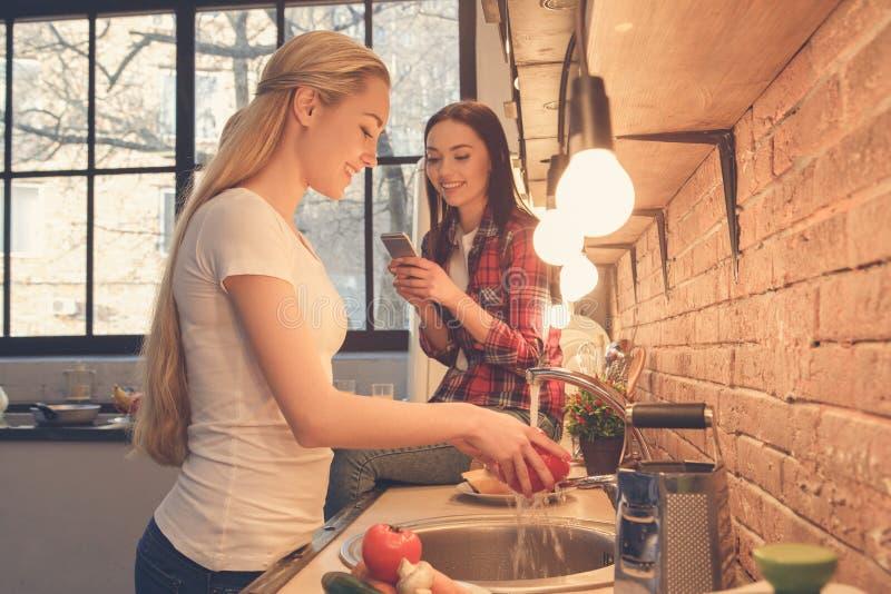 Amigos de las mujeres jovenes que cocinan la comida junto en casa imágenes de archivo libres de regalías