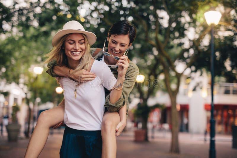 Amigos de las mujeres que llevan a cuestas y que gozan en la calle de la ciudad fotografía de archivo libre de regalías