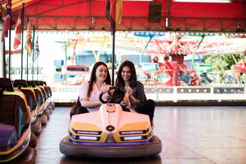 Amigos de las mujeres que se divierten en el parque de atracciones, coche de parachoques imagenes de archivo