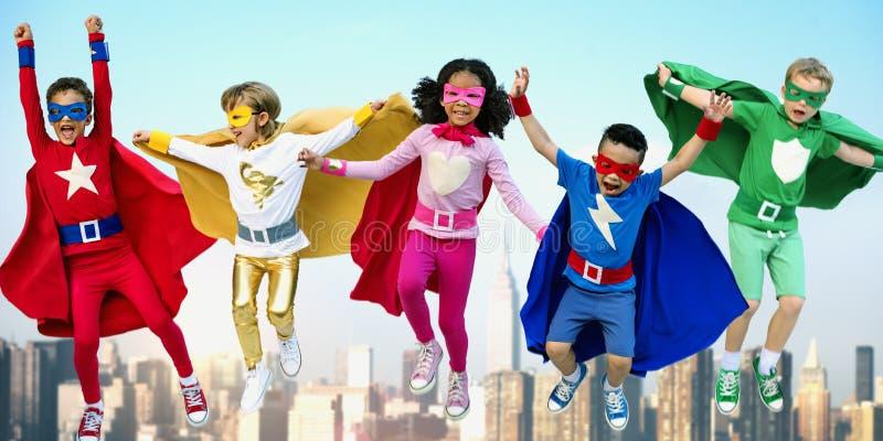 Amigos de los niños de los super héroes que juegan concepto de la diversión de la unidad foto de archivo libre de regalías