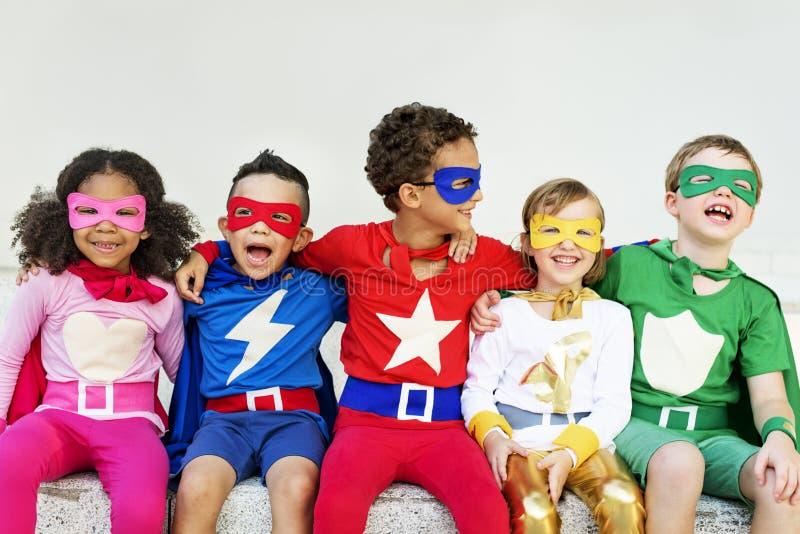 Amigos de los niños de los super héroes que juegan concepto de la unidad imágenes de archivo libres de regalías