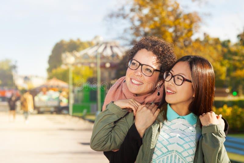 Amigos de muchachas felices que abrazan caminar en el parque del otoño fotos de archivo libres de regalías