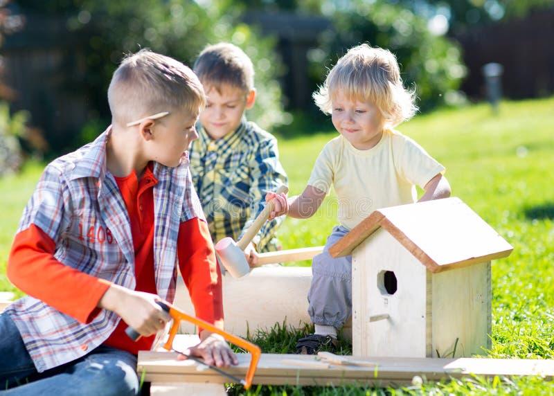 Amigos de rapazes pequenos que fazem a caixa-ninha de madeira no parque do verde do verão foto de stock royalty free