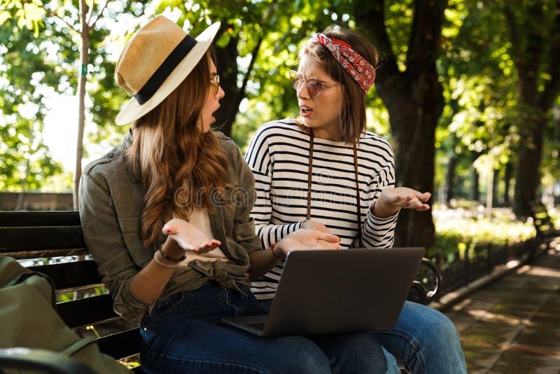 Amigos de senhoras desagradados confusos que sentam-se fora usando o laptop imagens de stock