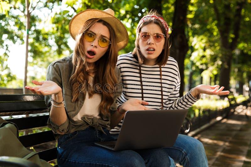 Amigos de senhoras desagradados confusos que sentam-se fora usando o laptop imagem de stock