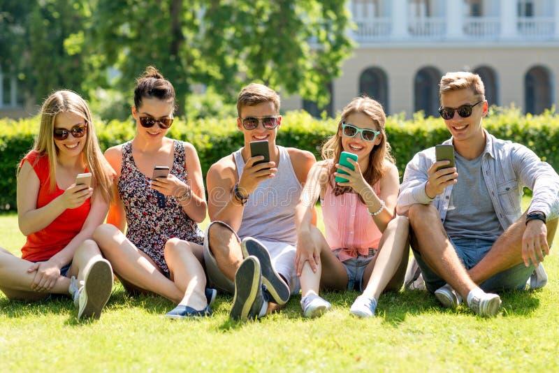 Amigos de sorriso com os smartphones que sentam-se na grama imagem de stock royalty free