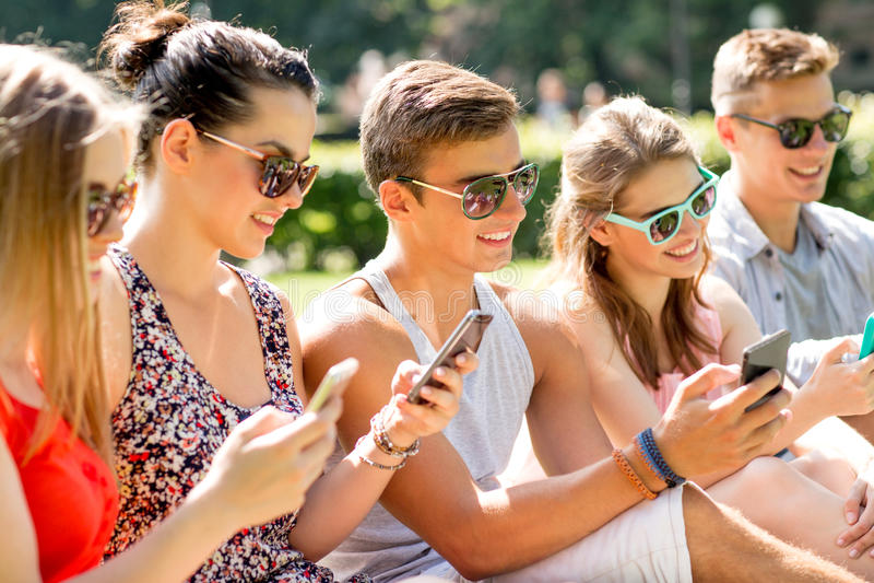 Amigos de sorriso com os smartphones que sentam-se na grama fotografia de stock royalty free