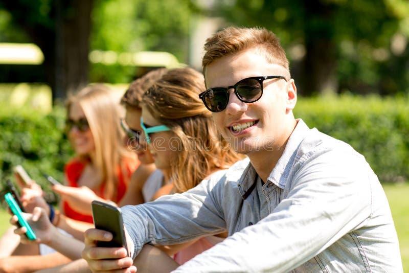 Amigos de sorriso com os smartphones que sentam-se no parque fotografia de stock royalty free