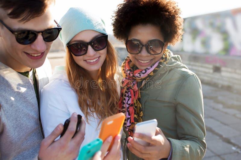 Amigos de sorriso com smartphones imagens de stock