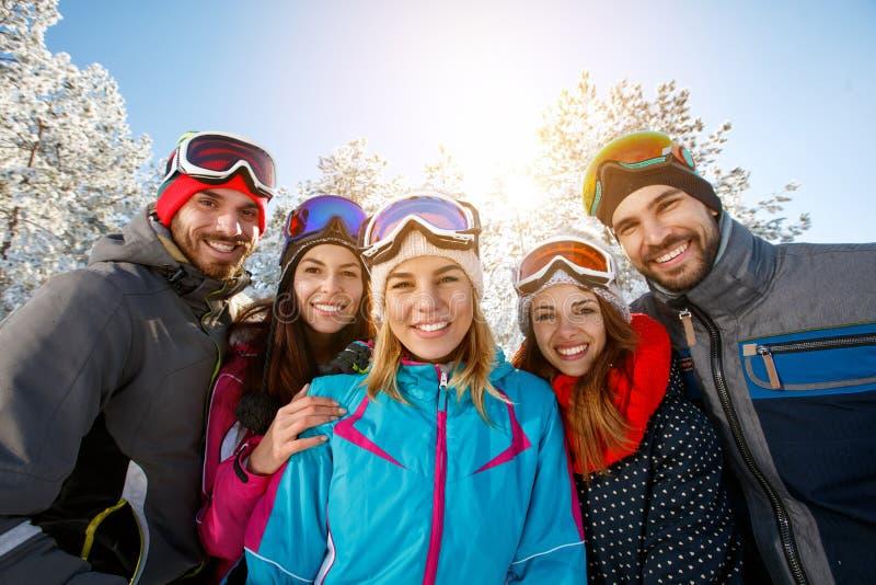 Amigos de sorriso em férias do inverno fotografia de stock royalty free