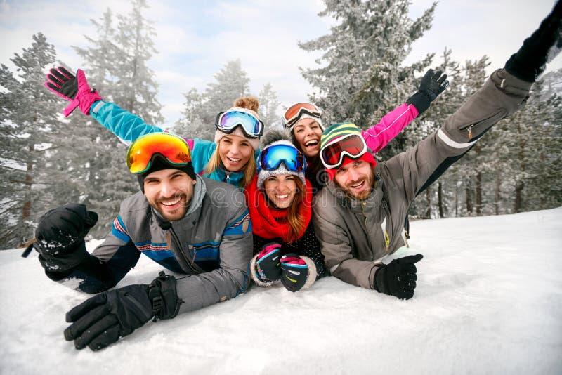 Amigos de sorriso em feriados de inverno - esquiadores que encontram-se na neve e no ha imagens de stock royalty free