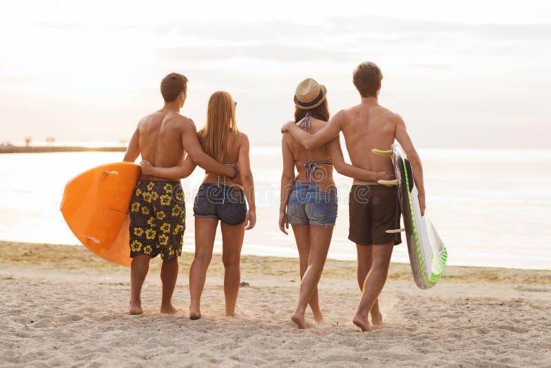 Amigos de sorriso nos óculos de sol com ressacas na praia fotografia de stock
