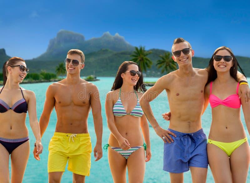 Amigos de sorriso nos óculos de sol na praia do verão imagem de stock