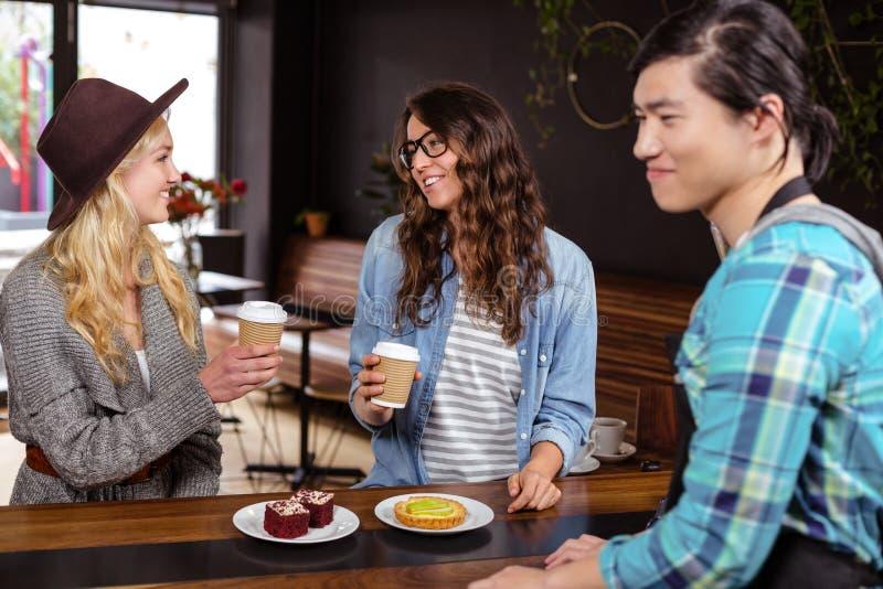Amigos de sorriso que apreciam o café e as pastelarias fotografia de stock royalty free