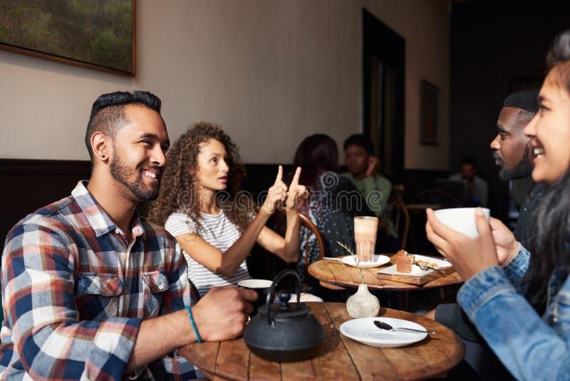 Amigos de sorriso que bebem o café ao sentar-se junto em um café fotografia de stock royalty free