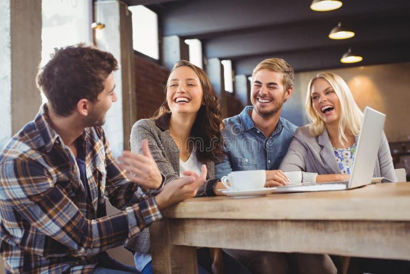 Amigos de sorriso que bebem o café e o riso fotos de stock