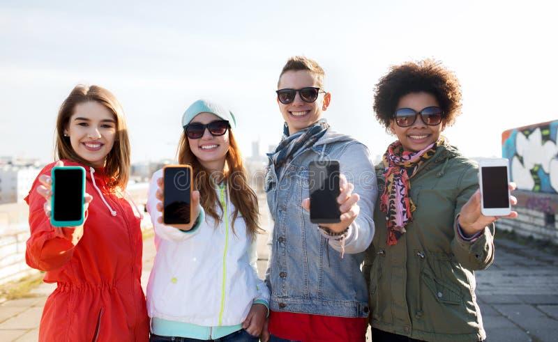 Amigos de sorriso que mostram telas vazias do smartphone fotos de stock royalty free
