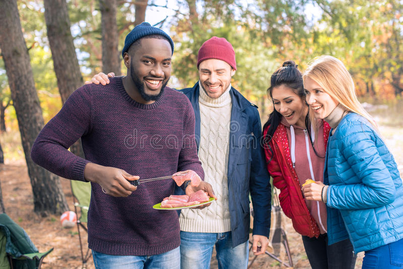 Amigos de sorriso que preparam o assado no parque imagem de stock royalty free