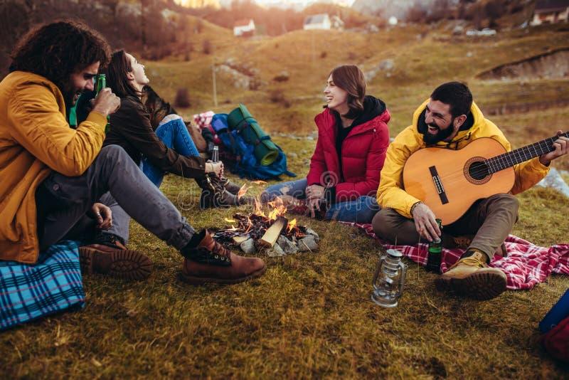 Amigos de sorriso que sentam-se em torno da fogueira no acampamento foto de stock