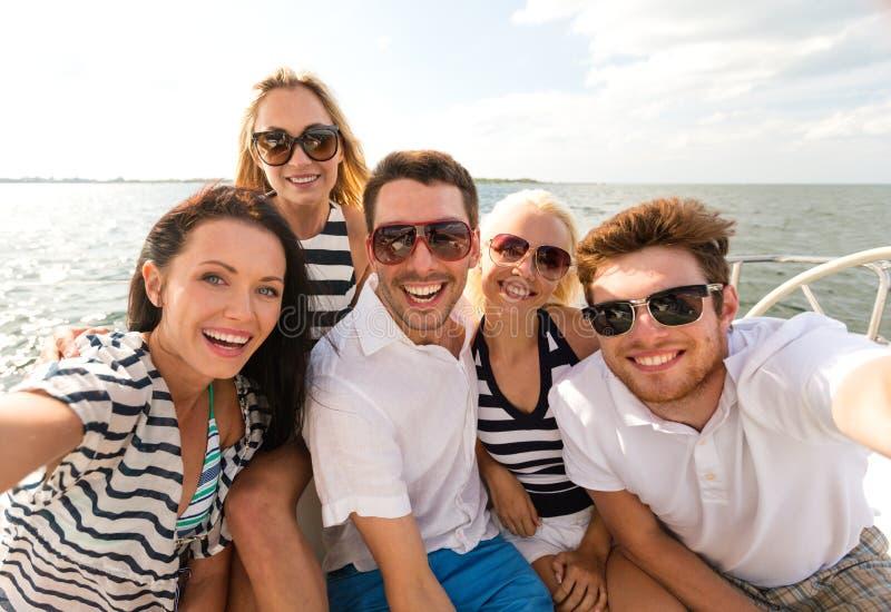 Amigos de sorriso que sentam-se na plataforma do iate imagem de stock royalty free