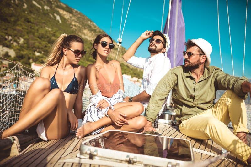Amigos de sorriso que sentam-se na plataforma e em ter do veleiro o divertimento foto de stock