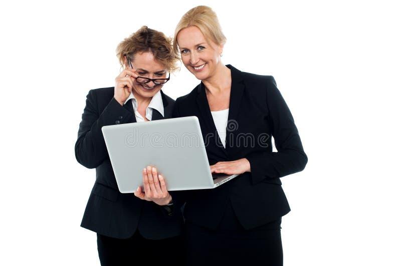 Amigos del asunto que disfrutan del vídeo en la computadora portátil imagenes de archivo