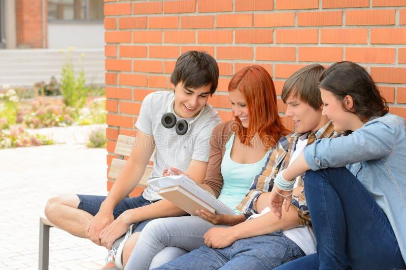 Amigos del estudiante que estudian junto el campus exterior imagen de archivo