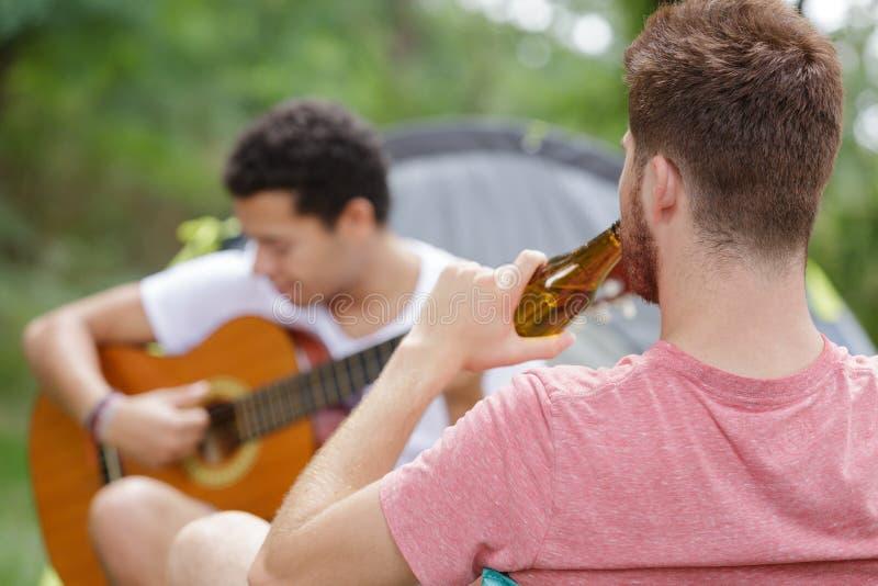 Amigos del grupo que tocan la guitarra foto de archivo libre de regalías