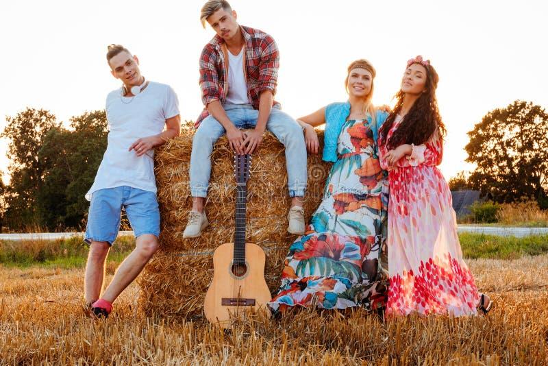 Amigos del hippie con la guitarra en un campo de trigo foto de archivo