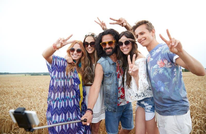 Amigos del hippie con smartphone en el palillo del selfie fotografía de archivo