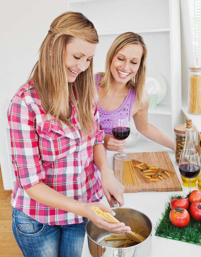 Amigos deleitados que cozinham spaghetties imagens de stock