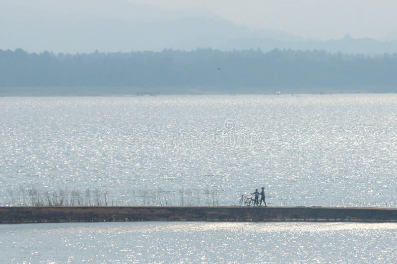 Amigos desportivos dos pares com bicicletas fora contra o lago fotografia de stock