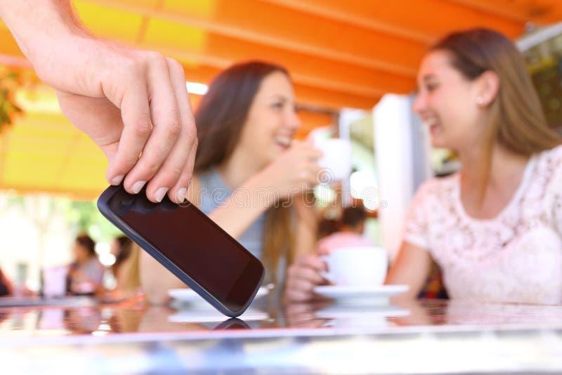 Amigos distraídos que hablan en una barra y un ladrón que roban el teléfono imagen de archivo libre de regalías