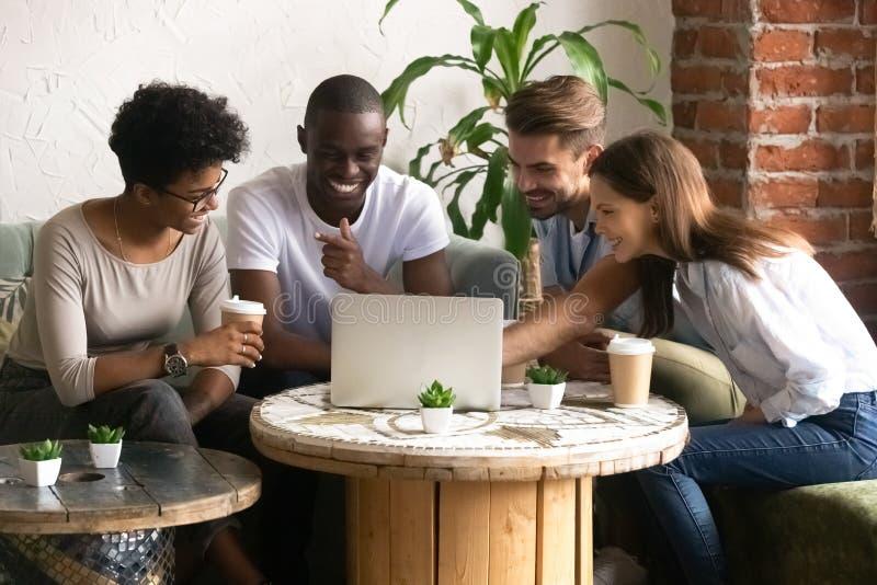 Amigos diversos de sorriso felizes que usam o portátil junto no café fotografia de stock royalty free