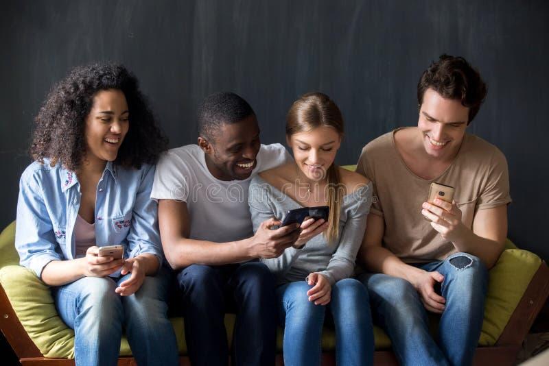 Amigos diversos de sorriso que discutem apps novos para o telefone celular fotos de stock royalty free